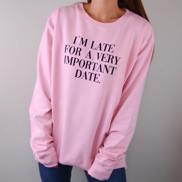 "Woman wearing pink sweater with black wording ""I'm late for a very important Date"" on the front. By Original Monkey Gifts."