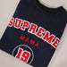 Woman wearing navy blue sweater with personalised Supreme Mama 19 in Red and white and is worn with blue denim jeans. By Original Monkey Gifts.