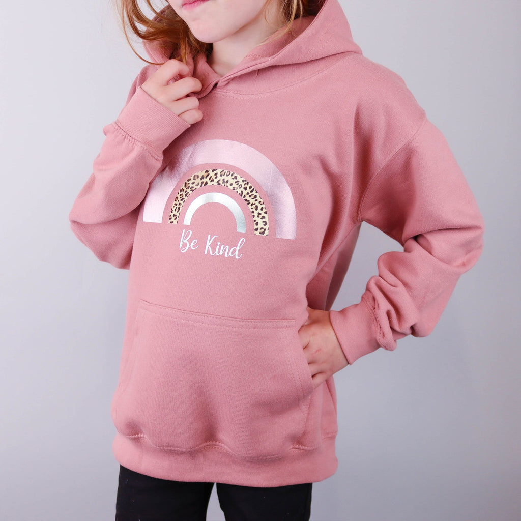 Child wearing a dusty pink hoodie with a rainbow print and saying be kind