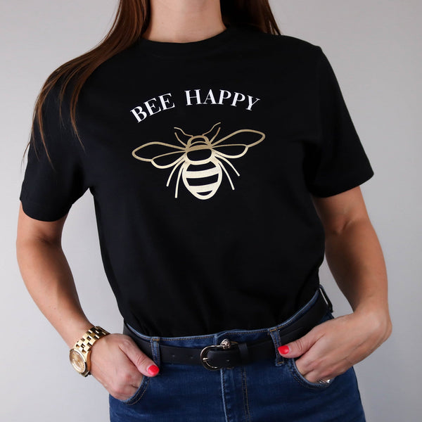 Woman wearing a black t shirt with a gold bee design and white text in a curve that reads 'bee happy' by Original Monkey Gifts. Woman also wears blue denim jeans, black leather belt and gold watch.