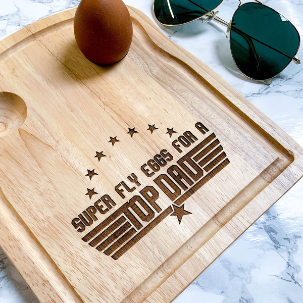 Egg board with message engraved that reads ' super fly eggs for a top dad' with stars by Original Monkey Gifts. Kitchen top with marble effect and sunglasses and also pictured.