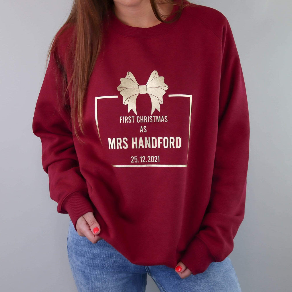 Woman wearing a burgundy sweater with gold text reading 'First Christmas as Mrs' and personalised with name and date. Also wearing blue denim jeans. By Original Monkey Gifts.