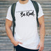 Man wearing a white t shirt with black writing that reads 'in a world where you can be anything... be kind' by Original Monkey Gifts. Man also wears black denim jeans and khaki green rucksack.