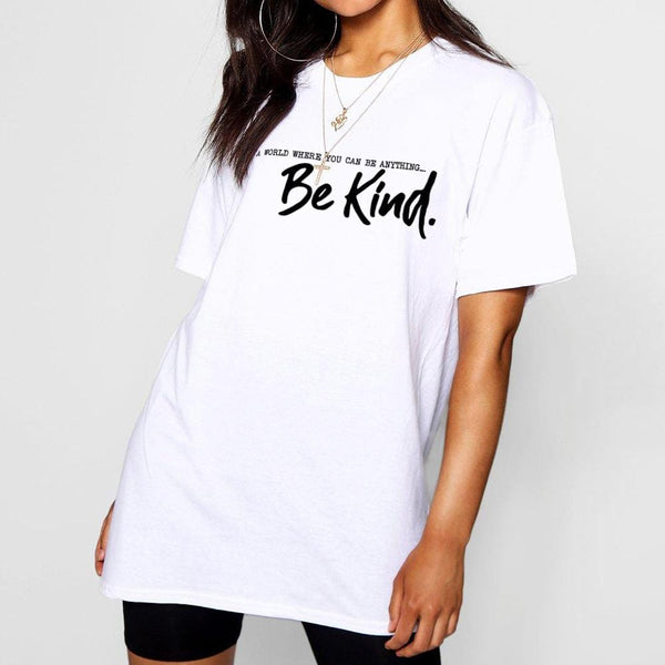 Woman wearing a white t shirt with black text that reads 'in a world where you can be anything.. be kind' by Original Monkey Gifts. Woman also wears black leggings and gold necklace.