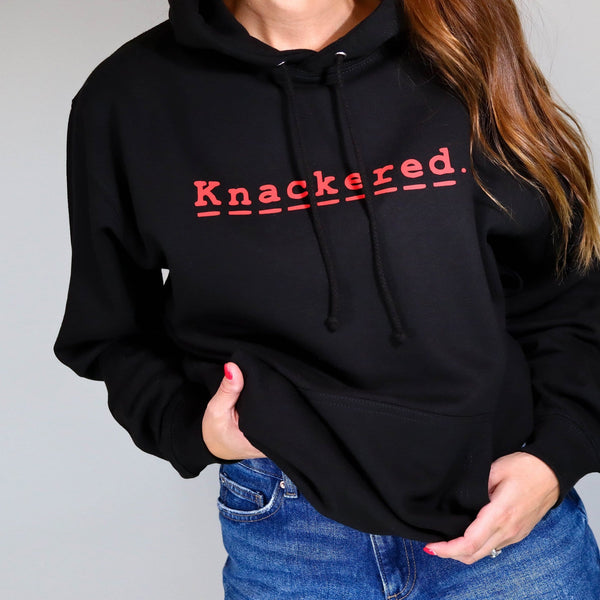 Woman wearing a black hoodie with red text reading knackered paired with blue denim jeans. By Original Monkey Gifts