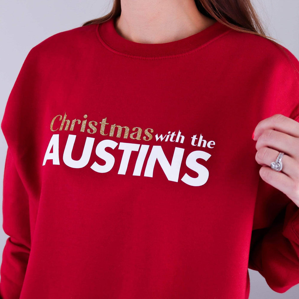 Woman wearing red jumper with text reading 'Christmas with the...' that can be personalised with any surname by Original Monkey. Woman also wearing black denim jeans and white gold wedding and engagement rings.