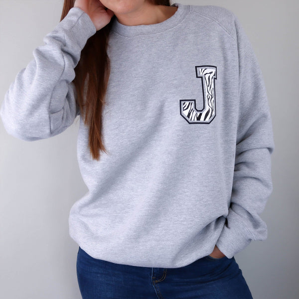 Woman wearing a grey raglan sweater with a zebra print J initial on the front, paired with blue denim jeans. Made by Original Monkey Gifts