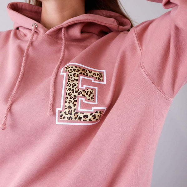 Woman wearing dusty pink hoodie with personalised letter E in Animal print text paired with blue denim jeans. By Original Monkey Gifts.