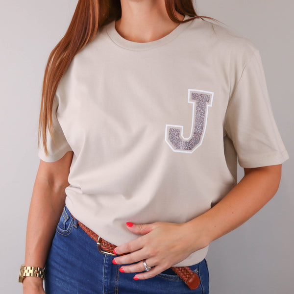 Woman wearing nude t shirt with a glittery initial 'J' on the left hand side by Original Monkey Gifts. Woman also wears blue denim jeans, brown leather belt and gold watch.