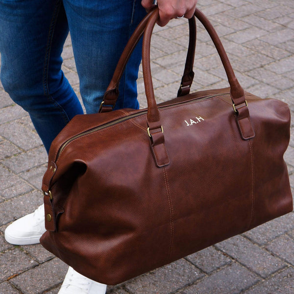 Man carrying a brown PU leather bag with personalised initials in gold by Original Monkey Gifts. Man wears blue denim jeans and white trainers.
