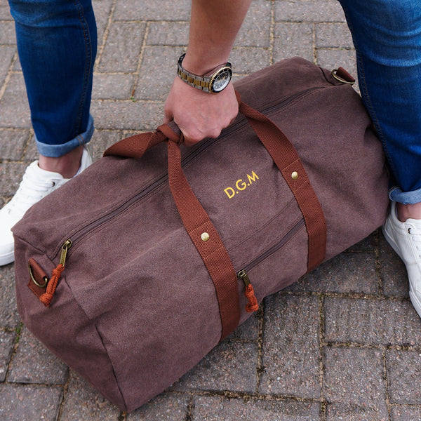 Man holding a canvas overnight bag in brown with personalised initial details in orange by Original Monkey Gifts.