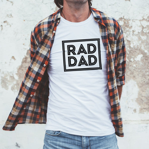 Man wearing a white T shirt with text that reads 'rad dad' in black by Original Monkey Gifts. Man also wears gingham orange shirt and blue denim jeans.