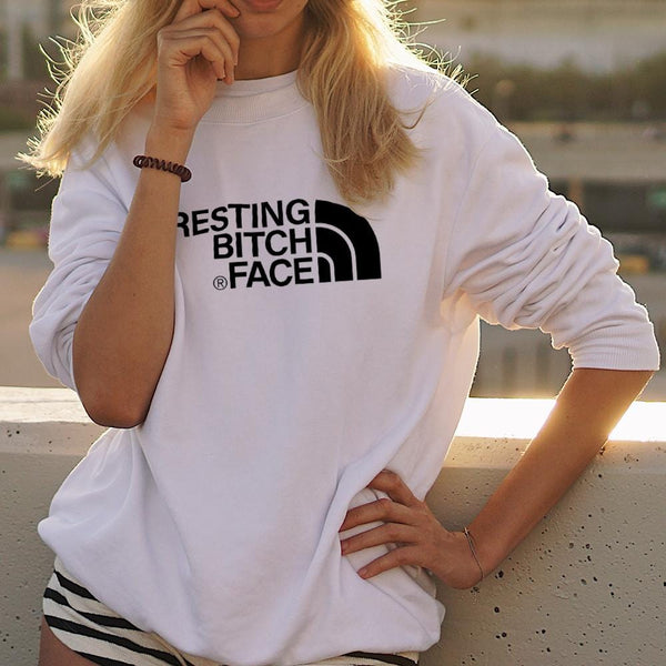 Woman wearing white sweater with resting bitch face written in black across the front. By Original Monkey Gifts
