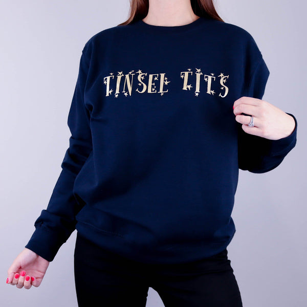 Woman wearing a navy sweater with gold writing that reads 'tinsel tits' made by Original Monkey Gifts.