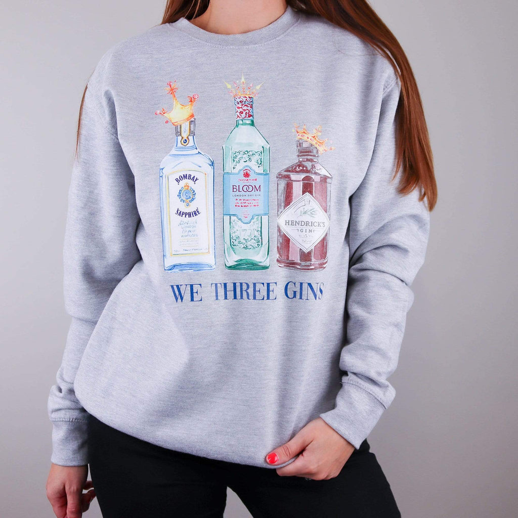 Woman wearing grey sweater with three gin bottles and crowns on with text reading 'we three gins' and black denim jeans by Original Monkey Gifts.