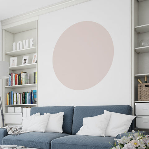 Blue sofa with a large dusky pink colour block circle above on a white wall.