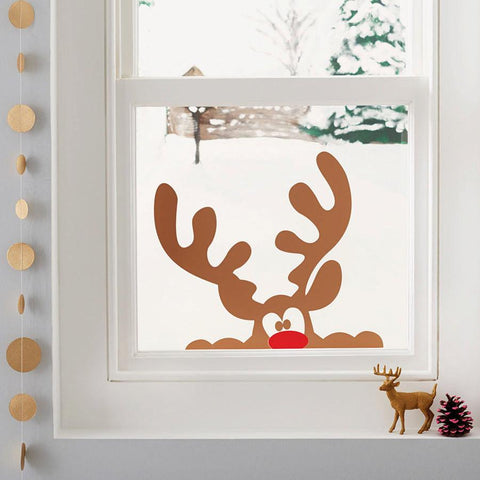 A Christmas window sticker of a cheeky brown reindeer peeping into the room, with his red nose just showing over the bottom of the window frame. It's snowing outside and there are other Christmas decorations around the window.