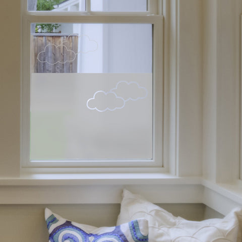 A window partially covered with frosted window film with a cloud design