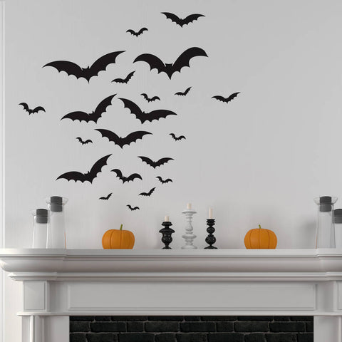 A white wall with a flock of black bat wall stickers over a white mantlepiece decorated for Halloween