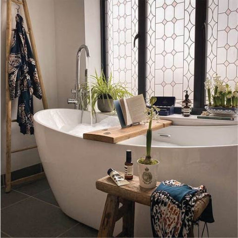 A bathroom with a freestanding modern white bath, with a black-framed window behind, covered in bespoke frosted window film