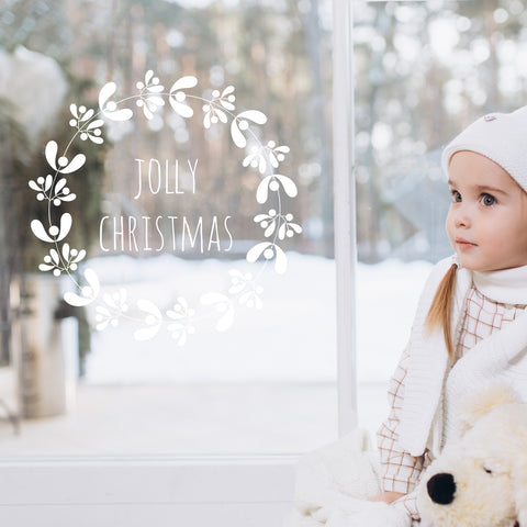 Girl standing next to a window with a white wreath-shaped window sticker with 'Jolly Christmas' written on it, in front of a snowy forest scene.