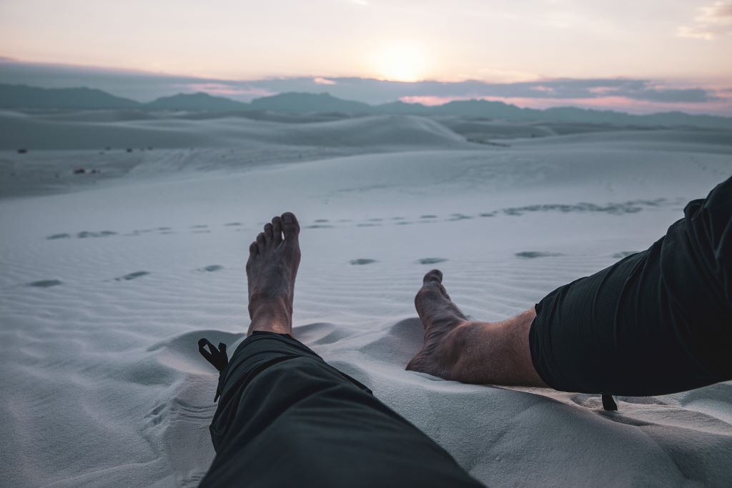 Picture of feet in desert sand at dawn