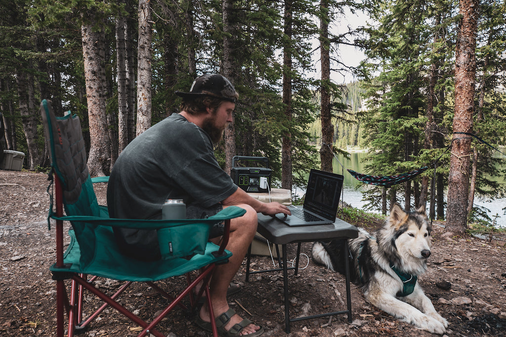 Jake sitting at camp working remotely with his dog