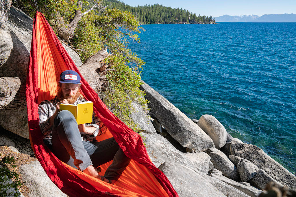 Man reading a book in a hammock on the shore of lake Tahoe