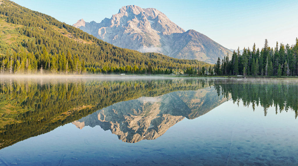 Lake reflecting the mountains and tree line