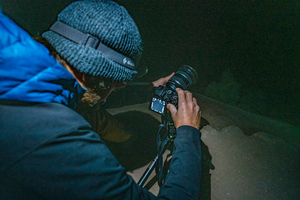 Man in grey beanie with his camera taking photos at night