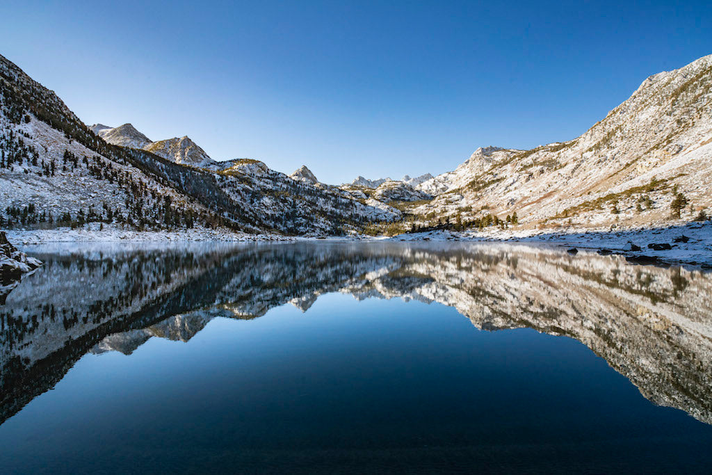 Rocky mountain dusted with snow reflecting on a lake