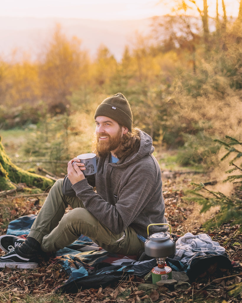 Guy sitting at his Campsite in a Camper Hooded Jacket