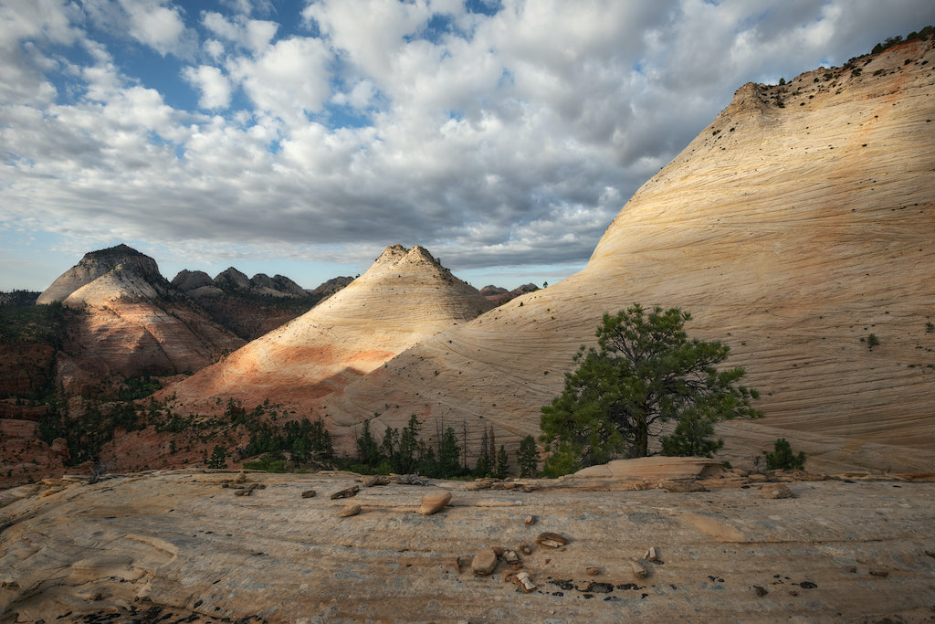 A pale pink mountain cascading into the horizon surrounded by a bright sky filled with puffy clouds