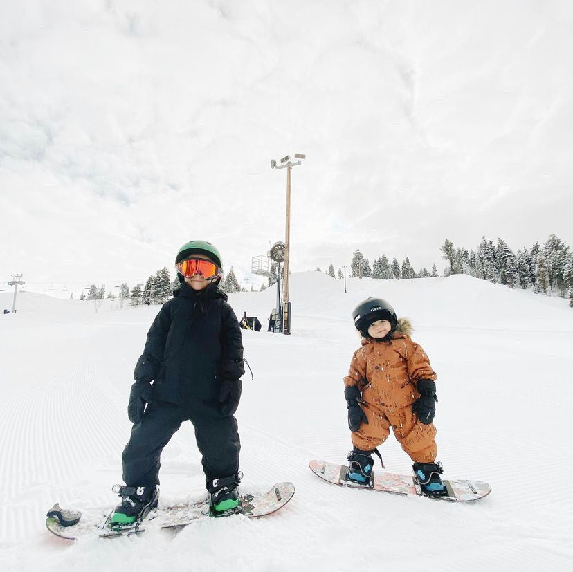 Two kids on the snowy mountains in their snowboarding gear