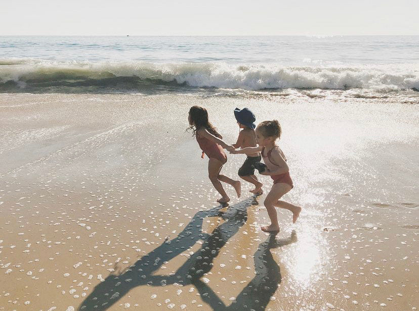 Image of three children playing one the shore