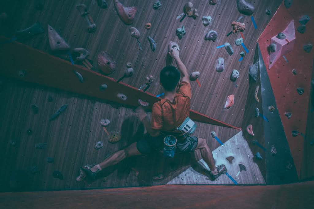 Guy in orange shirt rock climbing indoors at a gym