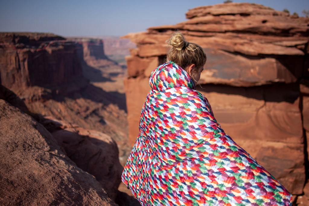 Girl wrapper in the Grandview Puffy Blanket in with the red rocks in the background