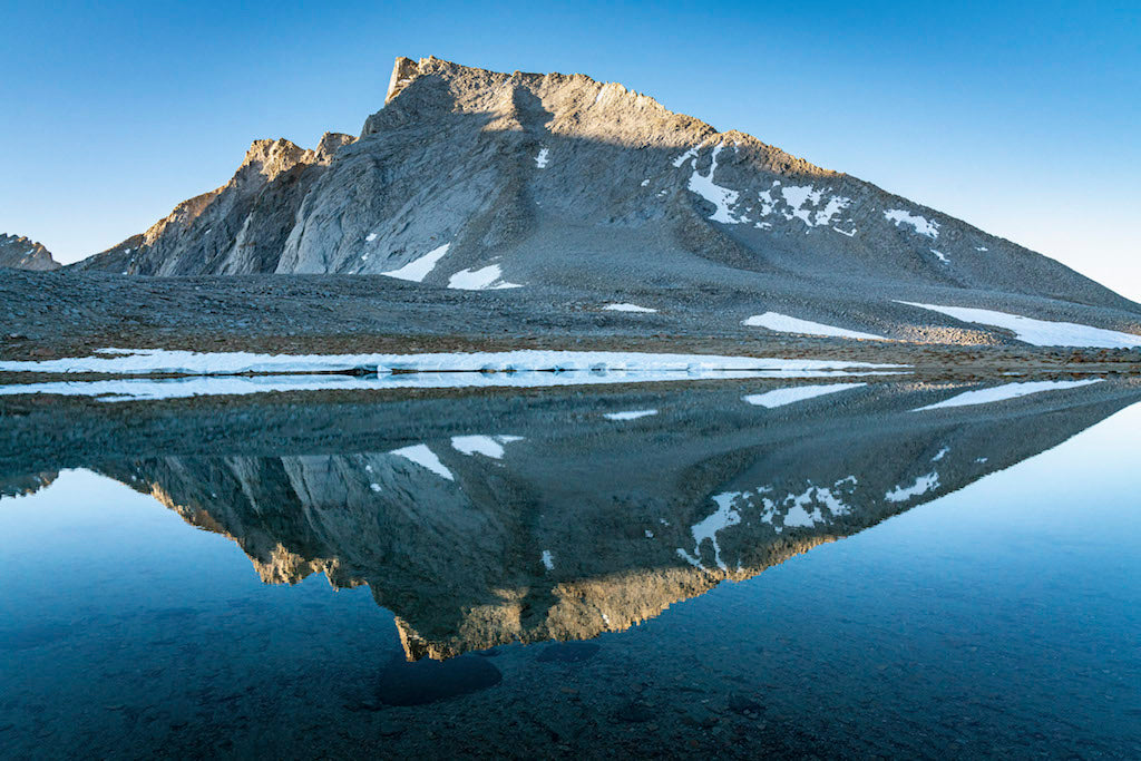 Rocky mountain dusted and reflecting on a lake