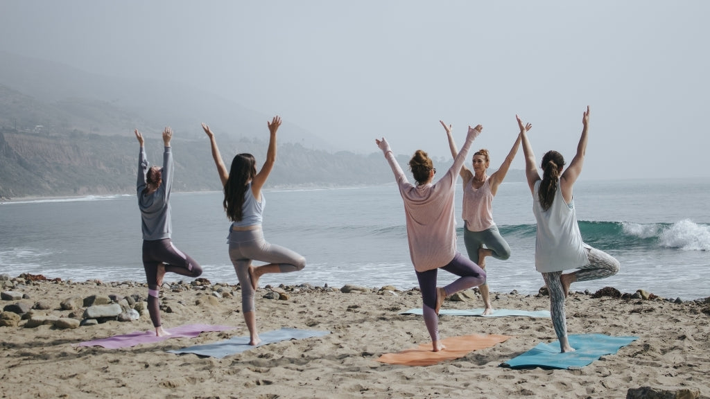 Many people doing yoga on the beach