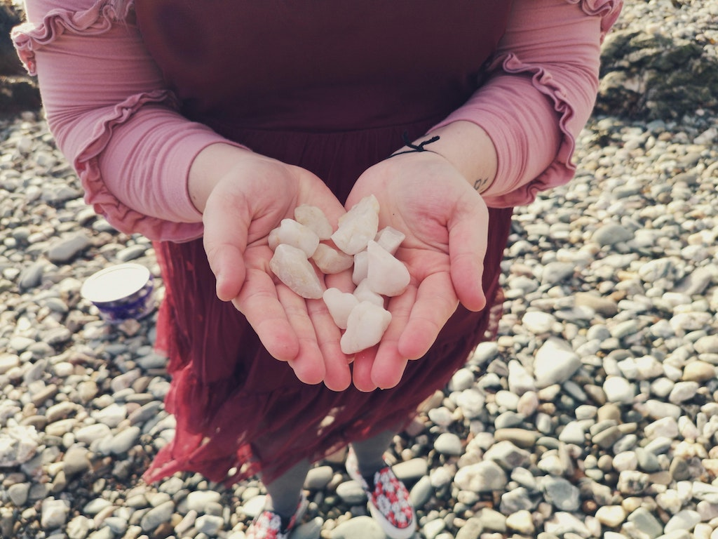 Photo of women holding a pile of rocks in her hand
