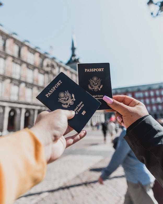 Two people holding up their passports