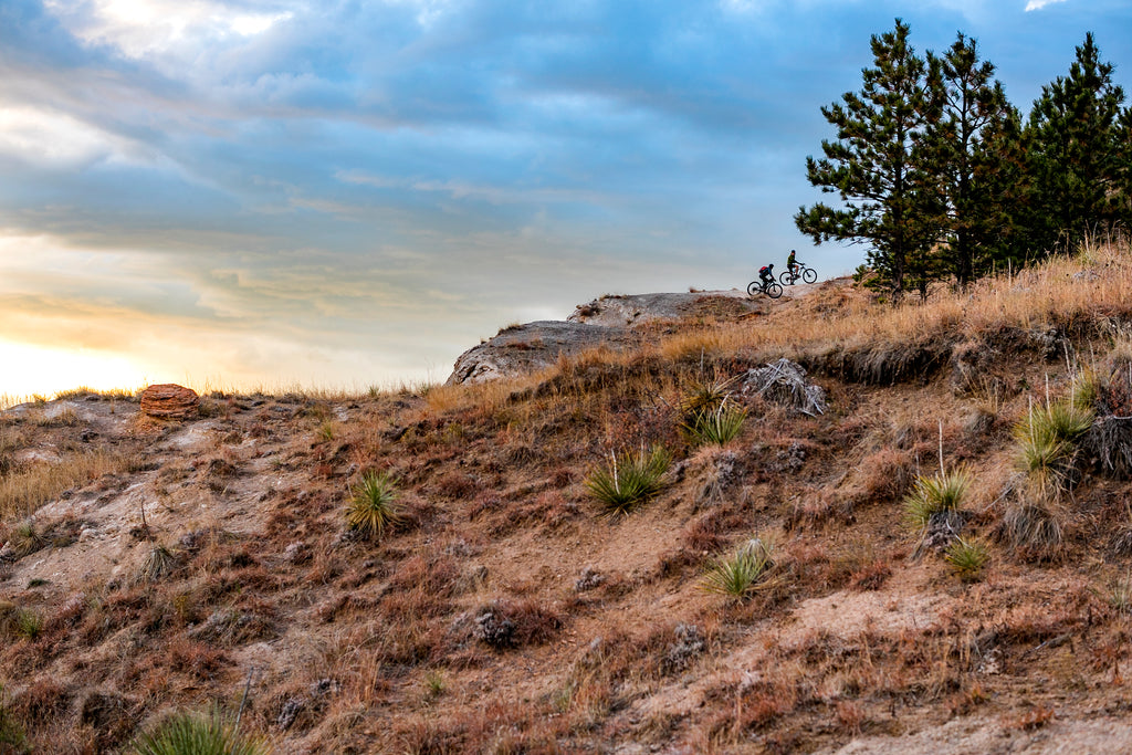 Two mountain bikers on a rocky ledge in Spearfish, South Dakota