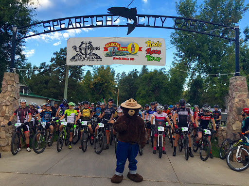 Mountain bikers line up at the start of the Dakota Five-0 with Smokey the Bear