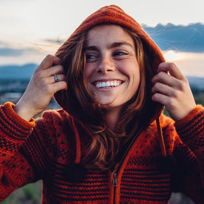 Woman wearing Everest Designs handcrafted Nepali wool orange sweater with the hood up