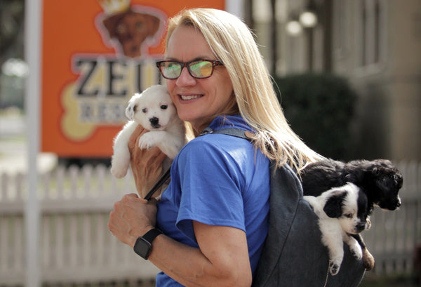 Michelle Ingram owner of Zeus Place and Zeus' Rescues in New Orleans Louisiana holds a rescue puppy and carries two puppies in the Pang Wangle Touring Convertible Backpack