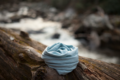 asheville, north carolina blue journey scarf on a log over a stream