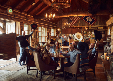 Brush Creek Ranch lodge with guests tipping their hats