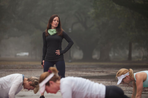 Outdoor fitness trainer Caroline Brady watches as her class does planks under the oak trees in Audubon Park in New Orleans.