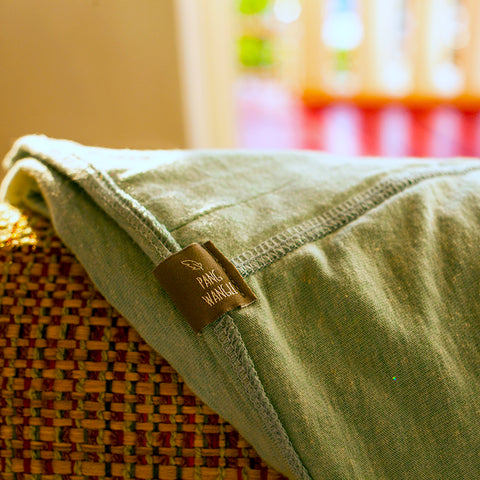 close up of pang wangle journey scarf with logo label in soda pop green recycled soda bottles and cotton blend