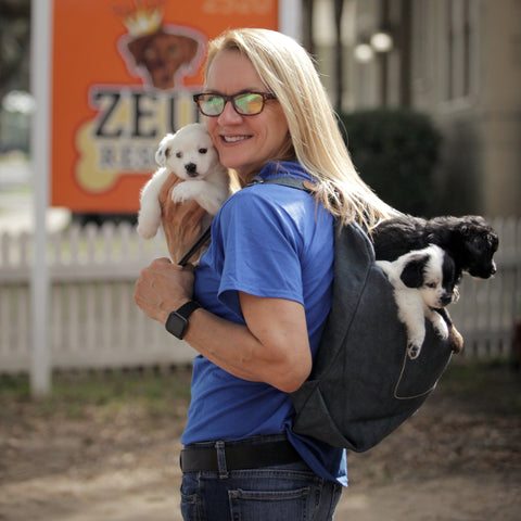 Michelle Ingram owner of Zues Place and Zues Rescues in New Orleans, Louisiana holds puppies in the Pang Wangle Touring Convertible Backpack